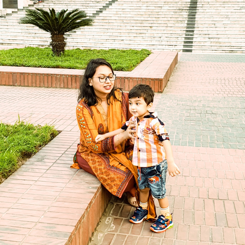 A Bangladeshi mom blogger named the aboltabol maa with her son at a planetarium for a quality time. the abotabol maa is wearing a yellow kurti and the baby is wearing a shirt with a short pant. he has spider man shoes. the aboltabol maa is a mom blogger from Dhaka Bangladesh. She is also called the royal bengal mom.
