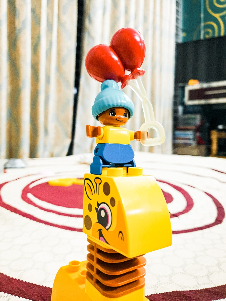 A lego Duplo set with a giraffe and a baby of color with yellow dress and blue pants. he has red balloons in his hands. the giraffe is an original lego animal set bought from toronto lego shop in canada. this is the lego set of Tuntun, son of The Aboltabol Maa, aka the royal bengal mom. She is a prominent writer in bangladesh who is one of the first mom bloggers in Bangladesh. She is a bangladeshi mom blogger from Dhaka