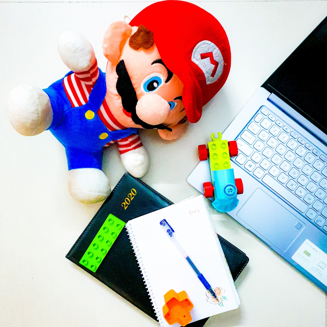 a stuffed toy of super mario with a notebook and a pen. there is a laptop and lego blocks of a toddler. this is a photo taken by a dhaka based mom blogger living in bangladesh. a feminist blogger