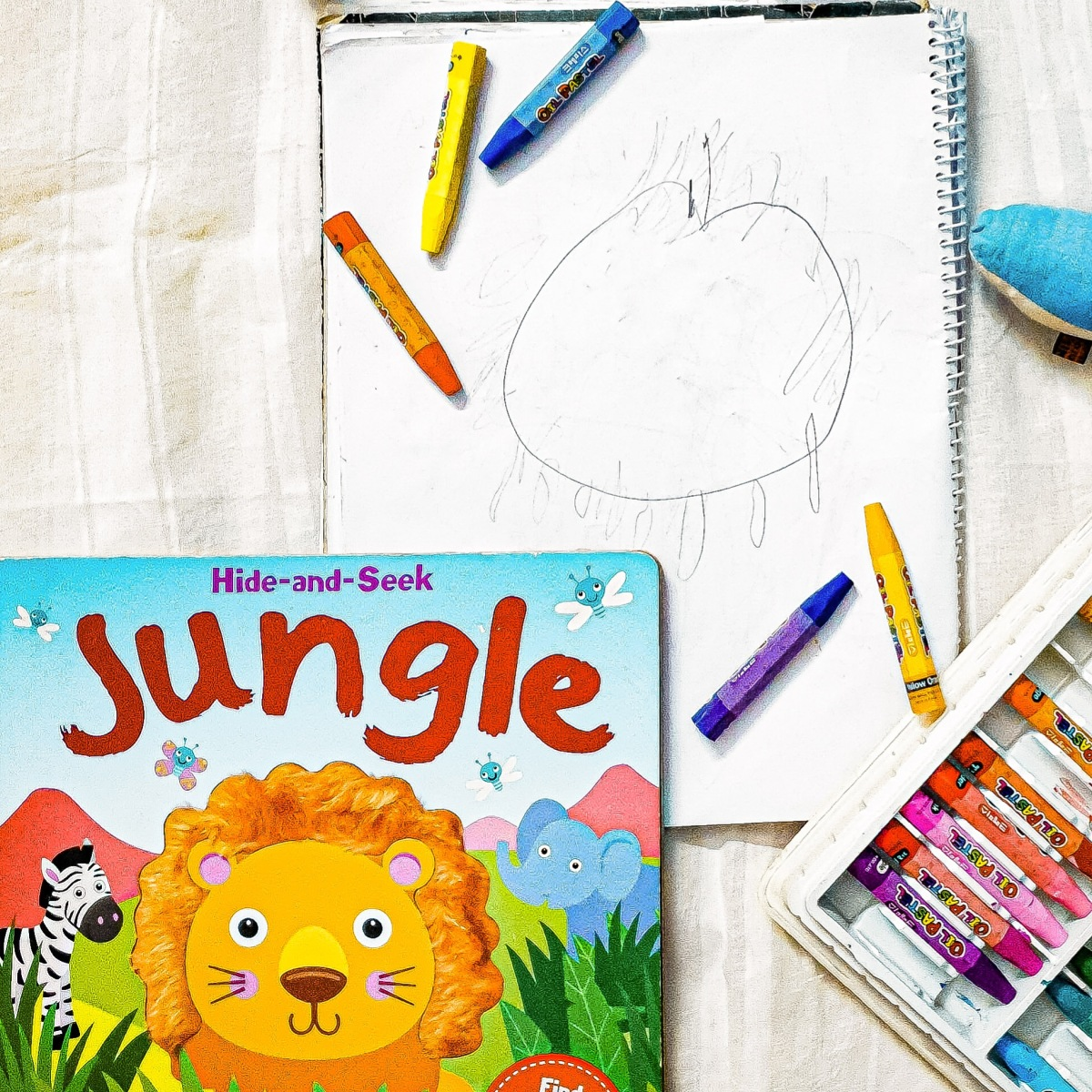A book with crayolas. a baby has drawn an image.